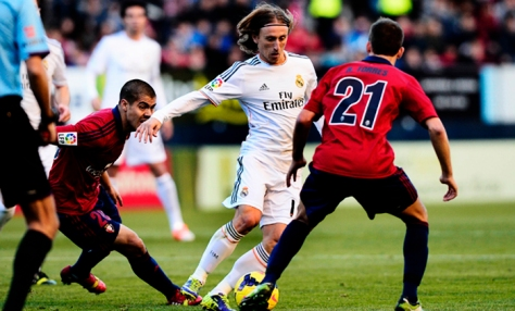 Real Madrid's Luka Modric (C) is challenged by Osasuna's Roberto Torres (R) during their Spanish first division soccer match at Reyno de Navarra stadium in Pamplona December 14, 2013. REUTERS/Vincent West (SPAIN - Tags: SPORT SOCCER) SOCCER-SPAIN/