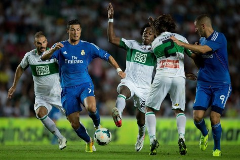 ELCHE, SPAIN - SEPTEMBER 25: Cristiano Ronaldo (2ndL) of Real Madrid CF competes for the ball with Carlos Sanchez (3dL) of  Elche FC and teammates Alberto Botia (L) and Damian Suarez as Karim Benzema (R) of Real Madrid CF follows them during the La Liga match between Elche FC and Real Madrid CF at Estadio Manuel Martinez Valero on September 25, 2013 in Elche, Spain.  (Photo by Gonzalo Arroyo Moreno/Getty Images)